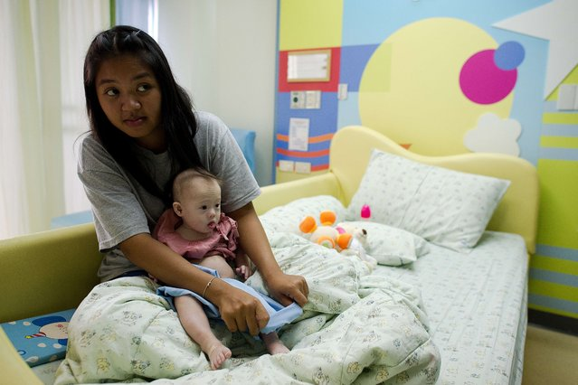 "Thai surrogate mother Pattaramon Chanbua (L) holds her baby Gammy, born with Down Syndrome, at the Samitivej hospital, Sriracha district in Chonburi province on August 4, 2014. The surrogate mother of a baby reportedly abandoned by his Australian parents in Thailand because he has Down Syndrome was a ""saint"" and ""absolute hero"", Australian Immigration Minister Scott Morrison said. (Photo by Nicolas Asfouri/AFP Photo)"