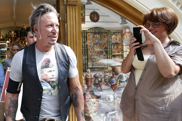 Actor Mickey Rourke (L) wears a T-shirt with an image depicting Russia's President Vladimir Putin, as a woman looks on at GUM department store in central Moscow, August 11, 2014. (Photo by Maxim Zmeyev/Reuters)