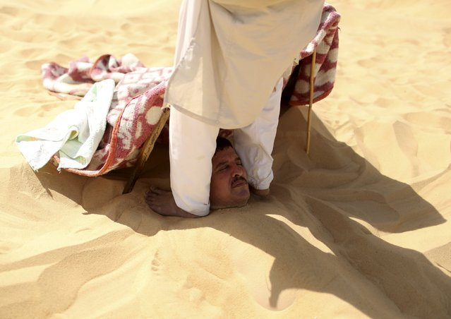 A worker gives a massage to a patient buried in sand by pressing on his shoulders with his feet in Siwa, Egypt, August 12, 2015. (Photo by Asmaa Waguih/Reuters)