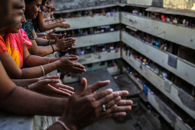 Indian people bang utensils and clap from the balconies of a residential building in Mumbai, India, 22 March 2020. Prime Minister Narendra Modi asks citizens to impose self-curfew to fight Coronavirus COVID-19 and also ask them to clap, bang the bells and utensils at 5pm Indian time to mark of respect and to thank the medical staff and others working 24 hours, during Covid-19 outbreak to keeping the Indians safe. (Photo by Divyakant Solanki/EPA/EFE)