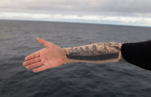 Derek Chambers from Belfast shows his tattoo of the Titanic, aboard the MS Balmoral Titanic memorial cruise ship in the Atlantic Ocean, on April 12, 2012. Nearly 100 years after the Titanic went down, the cruise with the same number of passengers aboard set sail to retrace the ship's voyage, including a visit to the location where it sank. (Photo by Lefteris Pitarakis/AP Photo)