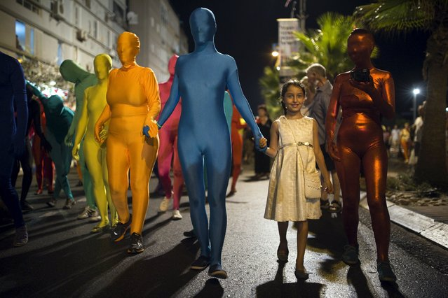 A group of people wearing full solid-coloured bodysuits walk along a promenade as they take part in a street art performance in Bat Yam, near Tel Aviv, Israel August 29, 2015. (Photo by Amir Cohen/Reuters)