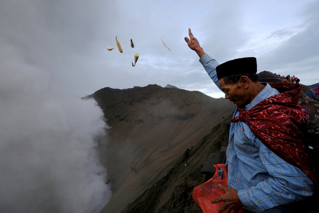 A Hindu worshipper throws offerings into the volcanic crater of Mount Bromo as smoke and ash rise from the volcano during the Kasada ceremony in Probolinggo, Indonesia, July 21, 2016. (Photo by Reuters/Beawiharta)