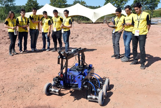 "Members of the Colombian team, from Bogota Uniandes University watch their ""Deimos"" Mars rover as they do final preparations before  the European Rover Challenge 2014 on September 5, 2014 in Checiny, Poland. 24 teams, from all over the world, have applied to step up to the Challenge which will be held from September 5 to 7 at the Regional Science-Technology Centre in Checiny. (Photo by Janek Skarzynski/AFP Photo)"