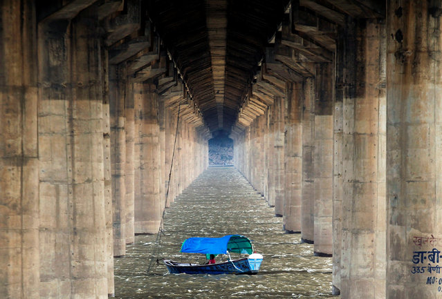 A man rests in a boat under a bridge over River Ganga in Allahabad, India, August 6, 2016. (Photo by Jitendra Prakash/Reuters)