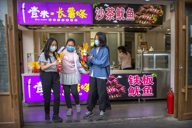 People wearing face masks to protect against the spread of the new coronavirus buy snacks at a shop on a pedestrian shopping street in Beijing, Saturday, May 16, 2020. According to official data released on Saturday India's confirmed coronavirus cases have surpassed China's. (Photo by Mark Schiefelbein/AP Photo)