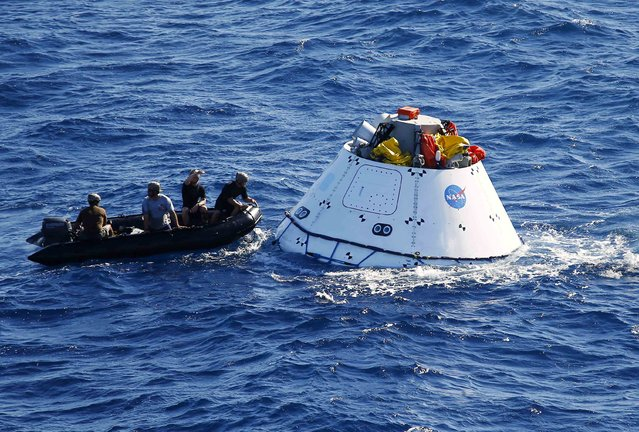 Recovery divers and crew from the USS Anchorage and NASA approach a test version of NASA's Orion capsule during a recovery drill off the coast of California September 15, 2014. Orion is NASA's next exploration spacecraft, designed to carry astronauts to destinations in deep space, including an asteroid and Mars. (Photo by Mike Blake/Reuters)