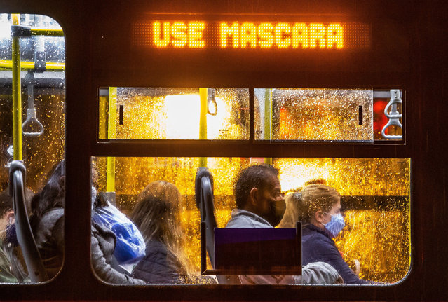 """Commuters wearing face masks travel on a public bus with an electronic sign reading """"Wear a face mask"""", in Curitiba, Brazil on May 22, 2020. Brazil, the hardest-hit Latin American country in the coronavirus pandemic, has surpassed 20,000 deaths, according to Brazil's Ministry of Health. (Photo by Daniel Castellano/AFP Photo)"""
