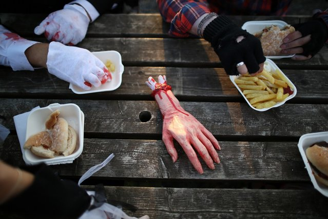 A fake hand sits on a picnic table as visitors to the Shocktober Fest enjoy a meal at Tulleys Farm  on October 6, 2012 in Turners Hill, England. People dressed as zombies from around the United Kingdom have converged on Tulleys Farm in an attempt to set a new Guinness World Record for the most zombies together in one place.  (Photo by Peter Macdiarmid)