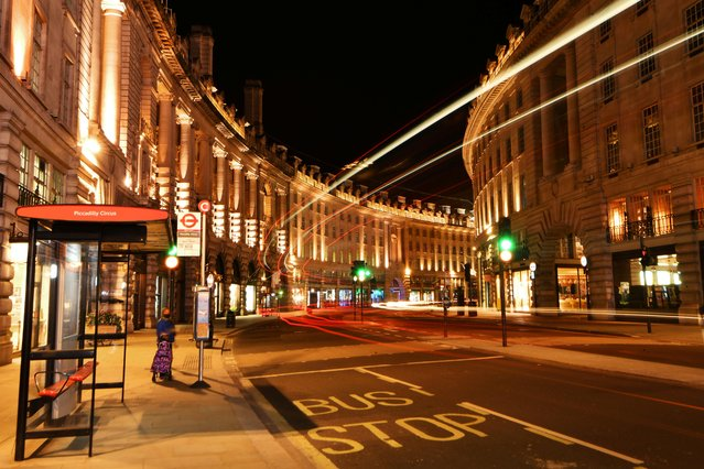 A woman waits for a bus on a quiet Regents Street during the late evening, as the city at night is deserted like never before while the coronavirus disease (COVID-19) lockdown continues, in London, Britain on April 21, 2020. (Photo by Dylan Martinez/Reuters)