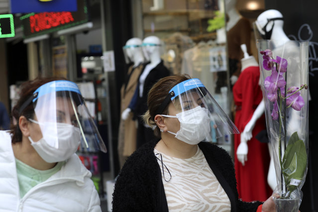 People wearing face masks for protection against the coronaviru, walk just hours before the start of a two-day curfew declared by the government in an attempt to control the spread of coronavirus, in Ankara, Turkey, Friday, May 8, 2020. (Photo by Burhan Ozbilici/AP Photo)