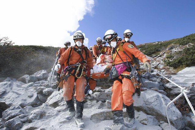 Firefighters carry a hiker during rescue operations on Mount Ontake, which straddles Nagano and Gifu prefectures, central Japan, in this handout photograph released by the Tokyo Fire Department and taken September 28, 2014. The death toll from Japan's volcanic eruption rose to 48 on Wednesday, the worst in 88 years, after more victims were discovered on the ash-covered summit. (Photo by Reuters/Tokyo Fire Department)