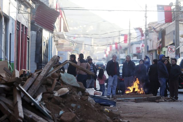 Chileans stand around a fire on a road after being evacuated from their homes following an 8.3 Ritcher scale magnitude earthquake, in Illapel, Chile, 17 September 2015. According to Chilean Ministry of the Interior at least five people have been killed and one million evacuated from their homes, particularly around the country's coastal areas for fear of a tsunami, following the massive earthquake. (Photo by Mario Ruiz/EPA)
