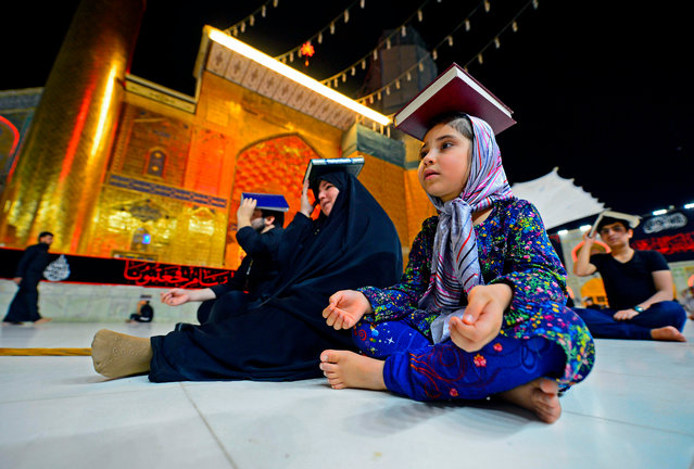 Shiite Muslims gather, albeit in fewer numbers due to the COVID-19 pandemic, at the Imam Ali shrine in the central Iraqi holy city of Najaf late on May 16, 2020, to mark Lailat al-Qadr, a night in the holy month of Ramadan during which the Koran was first revealed to the Prophet Mohammed in the seventh century. Worshippers placed copies of the Koran on their heads to convey veneration during the overnight prayers in a centuries-old ritual, as they pleaded to God to rid them of the ongoing novel coronavirus pandemic. (Photo by Haidar Hamdani/AFP Photo)