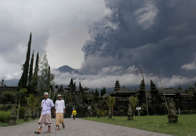 Balinese Hindus walk after praying as Mount Agung volcano erupts at Besakih Temple in Karangasem, Bali, Indonesia on November 26, 2017. (Photo by Johannes P. Christo/Reuters)