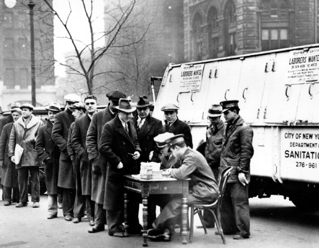 """Men line up in front of City Hall to apply for jobs cleaning away snow in New York City on January 3, 1934 during the Great Depression. A sign attached to the parked snow-removal truck reads, """"Laborers Wanted"""". (Photo by AP Photo)"""