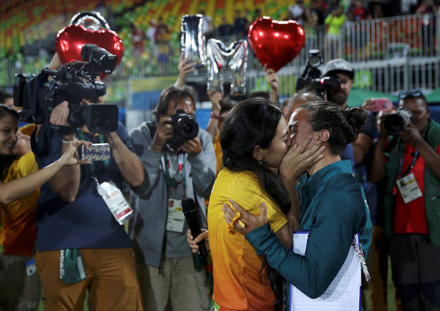 2016 Rio Olympics, Rugby, Women's Gold Medal Match Australia vs New Zealand, Deodoro Stadium, Rio de Janeiro, Brazil on August 8, 2016. Rugby player Isadora Cerullo (BRA) of Brazil kisses Marjorie, a volunteer, after receiving her wedding proposal on the sidelines of the women's rugby medal ceremony. (Photo by Alessandro Bianchi/Reuters)