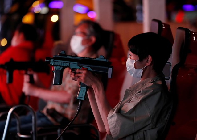 """Visitors wearing protective masks play shooting game at an indoor amusement park """"Joypolis"""" which reopened last weekend amid the coronavirus disease (COVID-19) outbreak in Tokyo, Japan on June 16, 2020. (Photo by Kim Kyung-Hoon/Reuters)"""