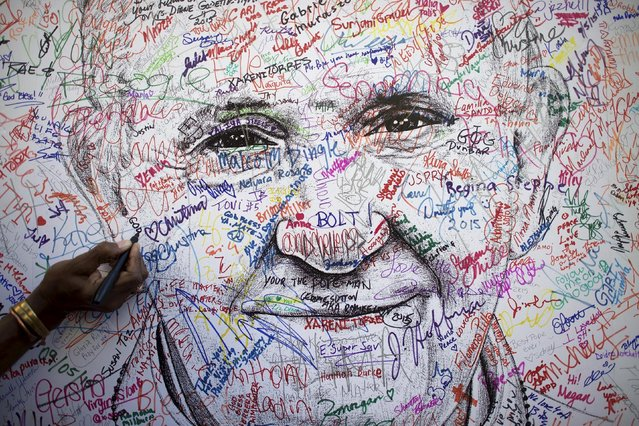 A pilgrim attending the World Meeting of Families signs a poster drawing of Pope Francis, by artist Mark Gaines, in Philadelphia, Pennsylvania, September 23, 2015. (Photo by Mark Makela/Reuters)