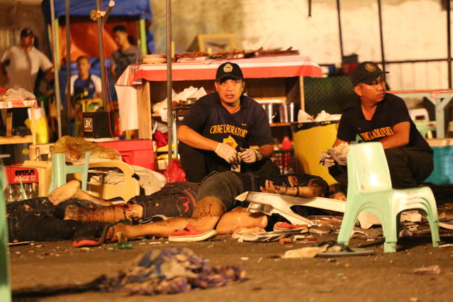 Philippine police investigators check bodies at a blast site at a night market that has left at least several people dead and wounded others in southern Davao city, Philippines late Friday September 2, 2016. The powerful explosion at a night market late Friday in Philippine President Rodrigo Duterte's hometown in the southern Philippines took place amid a security alert due to a major offensive against Abu Sayyaf militants in the region, officials said. (Photo by Manman Dejeto/AP Photo)