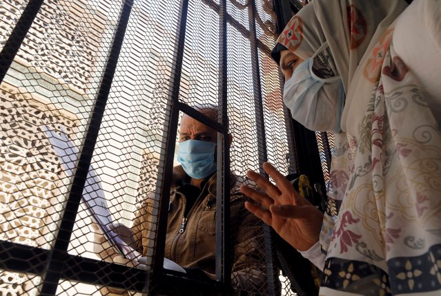 A man who is in a contact with people who have contracted the coronavirus disease (COVID-19) wears a protective face mask as he receives through iron bars the free medicines provided by the ministry of health, at a medical centre in Cairo, Egypt on June 3, 2020. (Photo by Mohamed Abd El Ghany/Reuters)