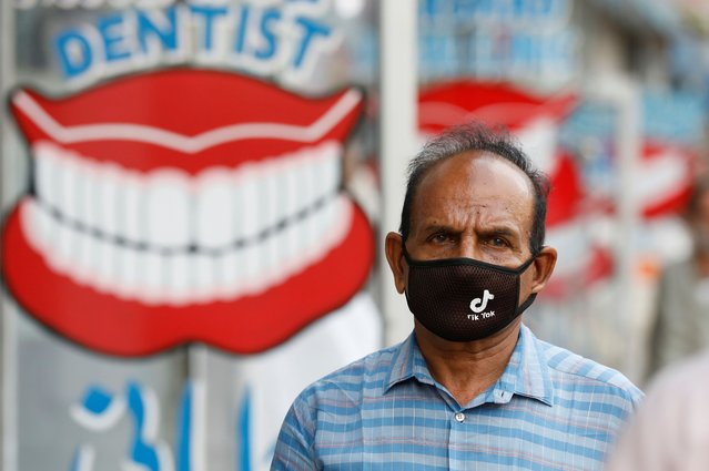 A man wears a protective face mask with the TikTok logo as he walks along dental shops, as the outbreak of the coronavirus disease (COVID-19) continues, in Karachi, Pakistan on July 14, 2020. (Photo by Akhtar Soomro/Reuters)