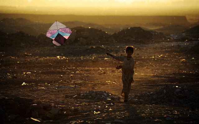 In this photograph taken on October 20, 2014, an Afghan child plays with a kite on the outskirts of Herat. Afghanistan's economy has improved significantly since the fall of the Taliban regime in 2001 largely because of the infusion of international assistance. Despite significant improvement in the last decade the country is still extremely poor and remains highly dependent on foreign aid. (Photo by Aref Karimi/AFP Photo)
