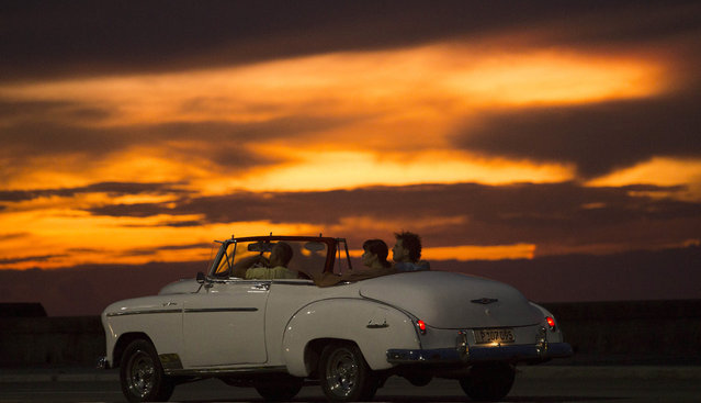 Tourists ride a vintage American convertible during sunset on the Malecon in Havana, Cuba, Wednesday, September 30, 2015. (Photo by Desmond Boylan/AP Photo)