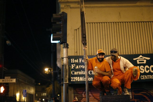Revellers squat by a street sign in celebration in San Francisco, California October 29, 2014. (Photo by Stephen Lam/Reuters)