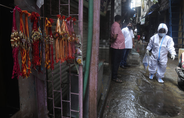 "Rakhi', or sacred thread is displayed for sale as a health worker arrives to screen residents for COVID-19 symptoms at Dharavi, one of Asia's biggest slums, in Mumbai, India, Monday, August 3, 2020. Marked the ""Raksha Bandhan"" festival when sisters tie the thread on the wrists of brothers. (Photo by Rafiq Maqbool/AP Photo)"
