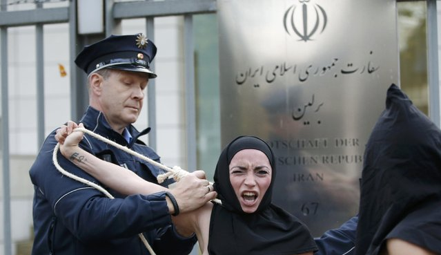 Police remove topless activists of women's rights group FEMEN during protest against the execution of an Iranian woman, outside the Iranian embassy in Berlin October 27, 2014. Reyhaneh Jabbari, 26, convicted of murdering a man she accused of trying to rape her as a teenager was hanged in Tehran on Saturday, the official news agency IRNA said, despite international pleas for her life to be spared. (Photo by Fabrizio Bensch/Reuters)