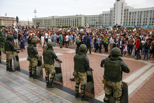 People gather in front of soldiers guarding the Belarusian Government building during a rally in Minsk, Belarus, Friday, August 14, 2020. (Photo by Sergei Grits/AP Photo)