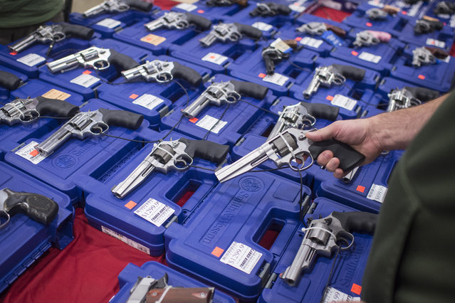 People look at handguns as thousands of customers and hundreds of dealers sell, show, and buy guns and other items during The Nation's Gun Show at the Dulles Expo Center which is the first major gun show in the area since the Oregon shooting in Chantilly, VA on Saturday, October 03, 2015. (Photo by Jabin Botsford/The Washington Post)