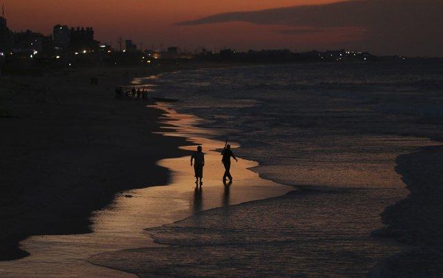 Palestinian fishermen walk along the beach of Gaza City October 22, 2014. (Photo by Mohammed Salem/Reuters)
