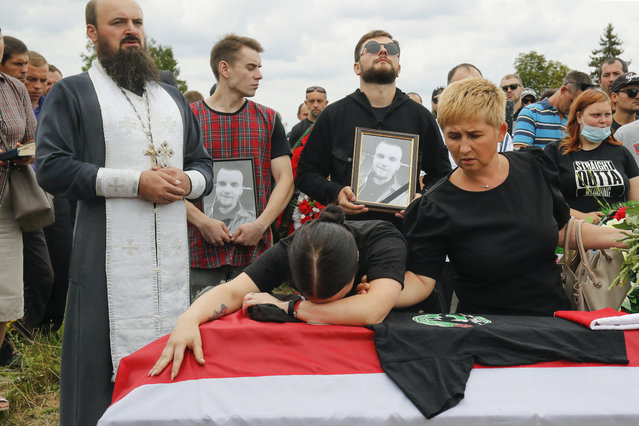 Elena, center left, reacts at the coffin of her husband Nikita Krivtsov during his funeral in the town of Molodechno, 70 km (46 miles) north-west of Minsk Molodechno, Belarus, Tuesday, August 25, 2020. Krivtsov went missing on Aug. 12 after taking part in protests and his body was found ten days. Police claim his death was by suicide.  His widow, Elena Krivtsevich, said she has sent a formal request to the Investigative Committee, the nation's top investigative agency, to launch a criminal inquiry into his death. (Photo by Dmitri Lovetsky/AP Photo)