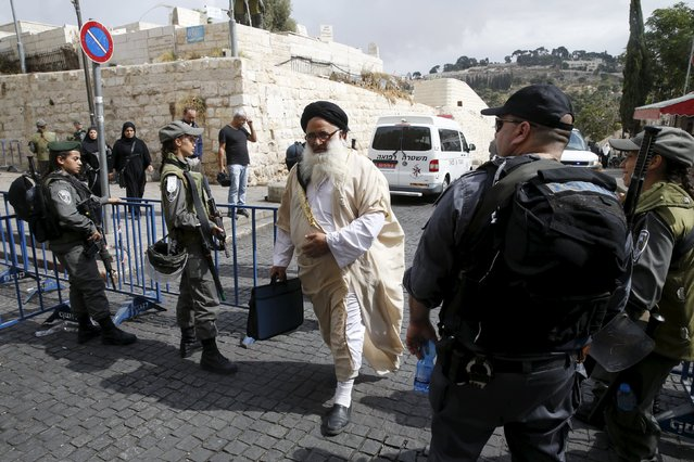 A Palestinian man walks past Israeli security personnel at an entrance to Jerusalem's Old City October 9, 2015. (Photo by Baz Ratner/Reuters)