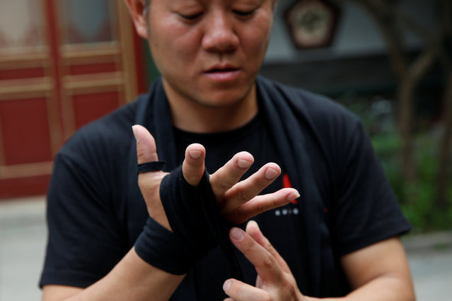 "Kung Fu master Xing Xi wears a glove before he starts training in mixed martial arts at his Kung Fu academy ""Kung Fu Zen"" in Beijing, China, July 3, 2016. (Photo by Kim Kyung-Hoon/Reuters)"