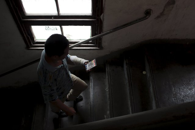Gao Haibao, looks at stock information on his mobile phone as he climbs the stairs to his apartment in Shanghai, China, July 23, 2015. Gao Haibao, a 55-year-old electrician who started trading stock in the 1990s, uses smartphones and computers to trade stocks from home. (Photo by Aly Song/Reuters)