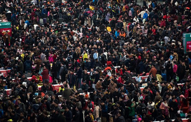 """Passengers crowd the Shanghai Hongqiao railway station as they wait to board their trains to head to their hometowns for the Lunar New Year holiday, in Shanghai on February 3, 2016. Over 2.9 billion trips will be made around China during the 40-day """"Spring Festival"""" travel rush, which kicked off on January 24, Chinese authorities estimated. The Spring Festival, this year being the Year of the Monkey. (Photo by AFP Photo/Stringer)"""