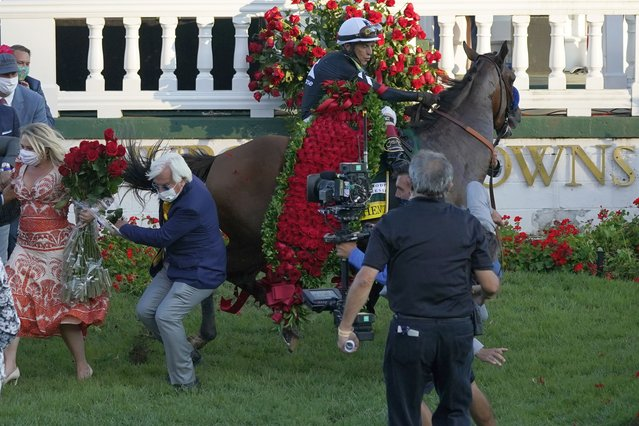 Trainer Bob Baffert is knocked to ground as Jockey John Velazquez try to control Authentic in the winners' circle after winning the 146th running of the Kentucky Derby at Churchill Downs, Saturday, September 5, 2020, in Louisville, Ky. (Photo by Jeff Roberson/AP Photo)