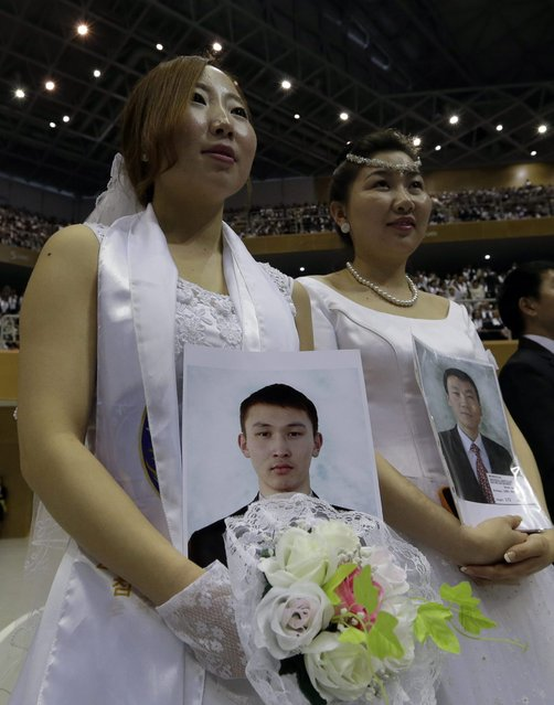 Mongolian bride Enkhzul Baatarchuluun, left, holds the picture of her groom Otgonbold Myagmardorj from Mongolia, who didn't appear, in a mass wedding ceremony at the CheongShim Peace World Center in Gapyeong, South Korea, Sunday, February 17, 2013. Some 3,500 South Korean and foreign couples exchanged or reaffirmed marriage vows in the Unification Church's mass wedding arranged by Hak Ja Han Moon, a wife of the late Rev. Sun Myung Moon, the controversial founder of the Unification Church. (Photo by Lee Jin-man/AP Photo)