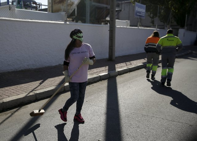 A s*x worker cleans the streets during a performance to denounce what they say is abuse and social stigma against them in Madrid, Spain, October 14, 2015. (Photo by Andrea Comas/Reuters)