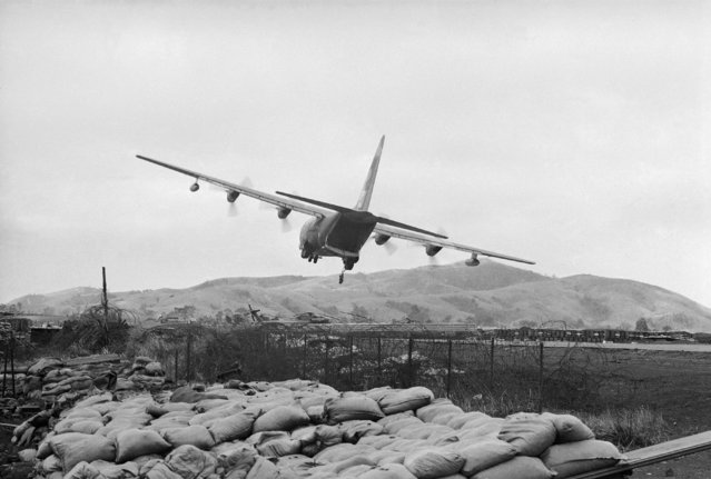 In this February 23, 1968, file photo, a U.S. Air Force transport plane drops supplies during a low-level pass over the U.S. Marine base at Khe Sanh, South Vietnam. In foreground is a sandbagged bunker on the base's perimeter. The planes avoid landing because of frequent Communist shelling. Early on the morning of Jan. 31, 1968, as Vietnamese celebrated the Lunar New Year, or Tet as it is known locally, Communist forces launched a wave of coordinated surprise attacks across South Vietnam. The campaign, one of the largest of the Vietnam War, led to intense fighting and heavy casualties in cities and towns across the South. (Photo by John Sneider/AP Photo)