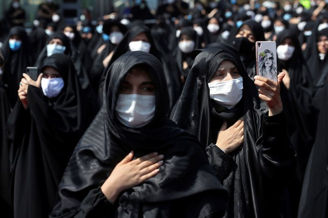 People wearing protective face masks to help prevent spread of the coronavirus mourn during an annual ceremony commemorating Ashoura, the anniversary of the 7th century death of Imam Hussein, a grandson of Prophet Muhammad, and one of Shiite Islam's most beloved saints, who was killed in a battle in Karbala in present-day Iraq, at the Saleh shrine in northern Tehran, Iran, Sunday, August 30, 2020. In Iran, which has the largest number of deaths from the coronavirus in the region, authorities allowed limited mourning rituals, urged social distancing and made wearing masks mandatory. (Photo by Ebrahim Noroozi/AP Photo)