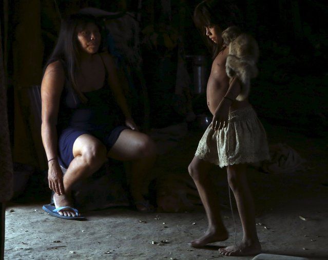 An indigenous girl (R) from the Kamayura tribe carries a monkey on her shoulders as she walks past her mother inside their house in their village at Xingu national park in Mato Grosso, Brazil, October 2, 2015. (Photo by Paulo Whitaker/Reuters)