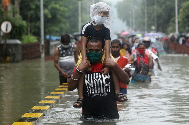 A man carries a child through a waterlogged road after heavy rainfall in Mumbai, India, September 23, 2020. (Photo by Francis Mascarenhas/Reuters)