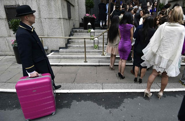 A hotel porter handles luggage as Miss World 2014 finalists enter a hotel during a publicity launch in central London November 25, 2014. (Photo by Toby Melville/Reuters)
