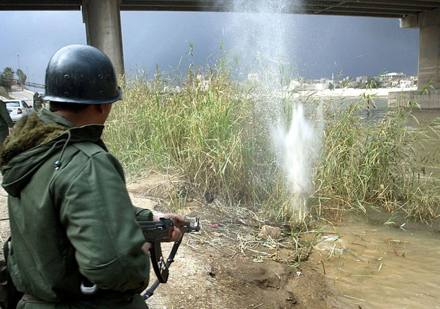 An Iraqi soldier fires his AK-47 rifle into reeds on the banks of the Tigris river in Baghdad, on March 23, 2003 after reports that U.S. or British pilots may have ejected over the city. Television reports showed Iraqi soldiers shooting into the Tigris river and in boats, apparently searching the water for pilots. (Photo by Goran Tomasevic/Reuters/The Atlantic)