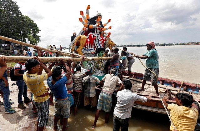 An idol of Hindu goddess Durga is being loaded onto a boat to transport it through the waters of river Ganga to a pandal, or a temporary platform, ahead of the Durga Puja festival in Kolkata, India, September 29, 2016. (Photo by Rupak De Chowdhuri/Reuters)