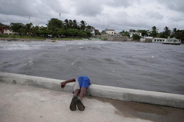 A boy tries to look under a pier ahead of Hurricane Matthew in Les Cayes, Haiti, October 2, 2016. (Photo by Andres Martinez Casares/Reuters)